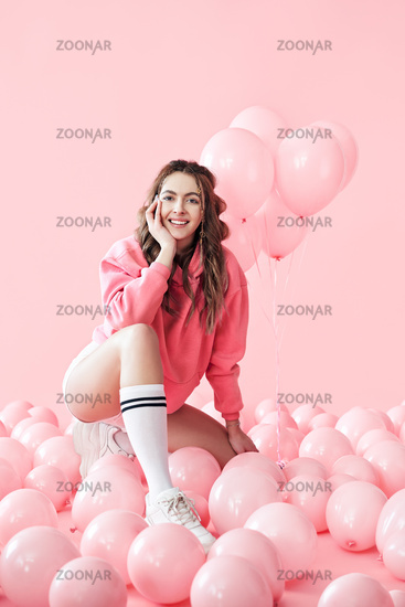 Young trendy woman posing with pink balloons on pink background