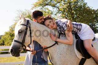 The young couple are having fun time with horse