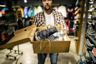 Store clerk helping customer try hiking boots at outdoors equipment shop. Salesman demonstrating trekking and hiking footwear for outdoor trails. Consultant help choose hiking boots in sports store