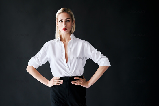 Fashion portrait of young trendy woman posing on black studio background
