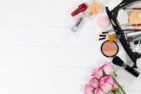 Make up view with pink flowers and perfume on white background