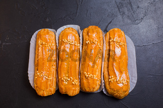 Sweet and delicious eclairs on black background