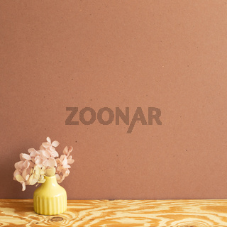 Vase of pink hydrangea flower on wooden table. brown wall background. copy space