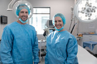 Portrait of caucasian male and female surgeons standing in operating theatre wearing face mask