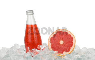 Glass bottle of pink grapefruit drink on ice