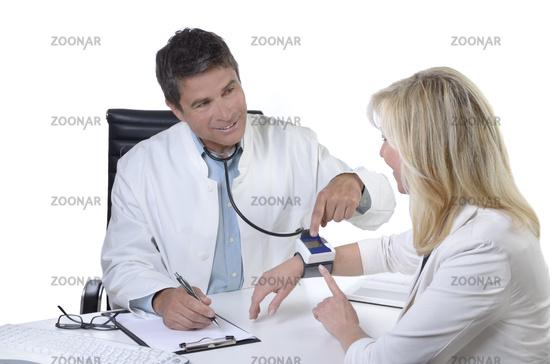 Arzt erklärt Patientin Blutdruckmessgerät