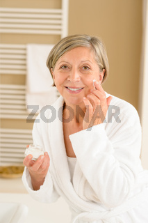 Senior woman with facial cream in bathroom