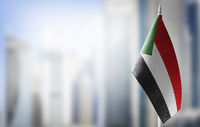 A small flag of Sudan on the background of a blurred background