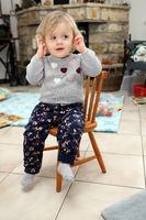 kleines Mädchen sitzt im Wohnzimmer auf einem Kinderstuhl aus Holz  und hält sich die Ohren zu
