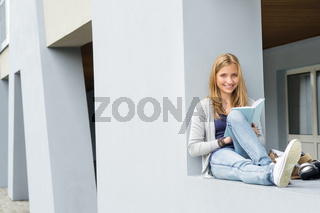 Teenage woman reading book outside of school
