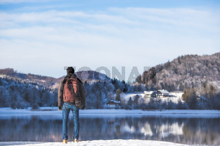 Outdoor adventure: Caucasian man is standing at the lakeshore and enjoys the view. Beautiful winter landscape, Austria