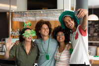 Diverse group of happy friends celebrating st patrick's day taking selfie at bar