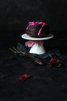 kleiner Browniekuchen mit pink Zuckerguss und getrockneten Blüten