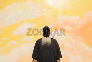 Summer portrait of mature man with long gray beard and sunglasses against cloudy background wall wearing face mask to protect from Covid-19