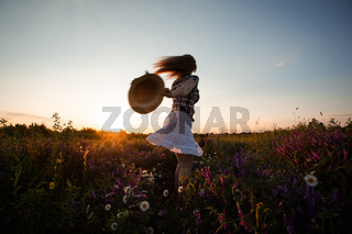 Cheerful and playful young female running in summer field