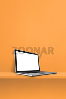 Laptop computer on orange shelf. Vertical background