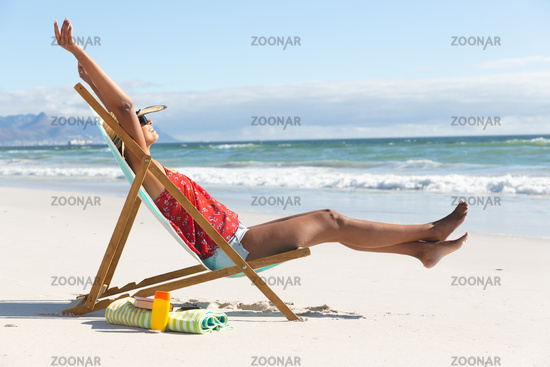 Mixed race happy woman on beach holiday sitting in deckchair stretching