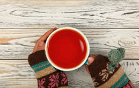 Woman hands hold full cup of black tea