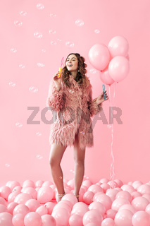 Young pretty woman blowing soap bubbles on pink background with balloons