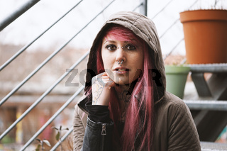 thoughtful young woman with piercings and tattoos sitting on outside staircase