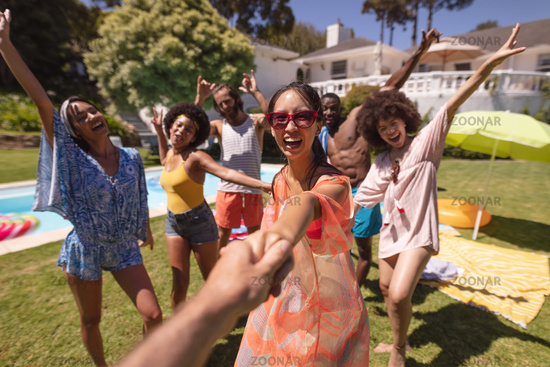 Diverse group of happy friends having fun dancing at a pool party