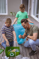 Caucasian father and two sons collecting plastic materials in a bag outdoors
