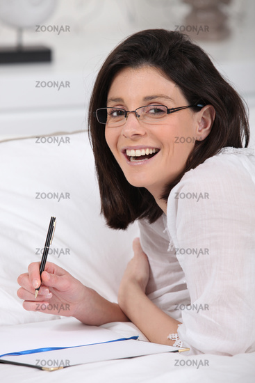 Smiling woman with notebook and pencil
