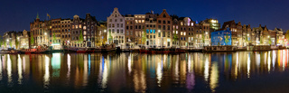 Panorama of the buildings along the canal at night in Amsterdam, Netherlands