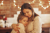 Mother and little daughter embracing hugging while sitting in room decorated for christmas holidays