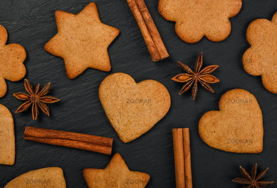 Gingerbread cookies and spices on black slate