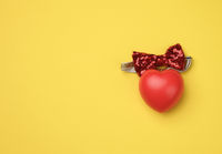 red rubber heart on a yellow background