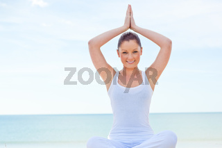 Portrait of young woman doing yoga exercise on the beach