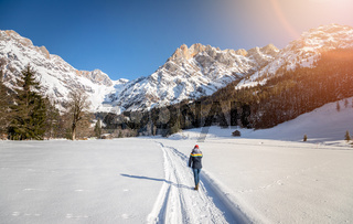Sunny winter landscape in the nature: Girl is walking on snowy footpath, mountain range, snowy trees, sunshine and blue sky