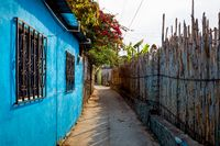 Sunlit alley with colorful house, flower bush and wooden fence in San Pedro la Laguna at lake Atitlan, Guatemala