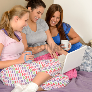 Three cheerful girls surfing on the net