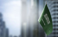 A small flag of Saudi Arabia on the background of a blurred background