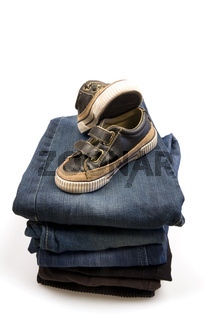 casual children's shoes putted on folded blue denim pants