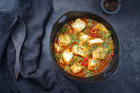 Modern style traditional Spanish seafood zarzuela de pescado with fish served in red sauce as top view in design pot