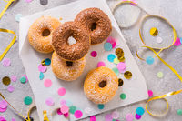 Donuts for carnival and party. Donuts with streamers and confetti. Colorful carnival or birthday image.