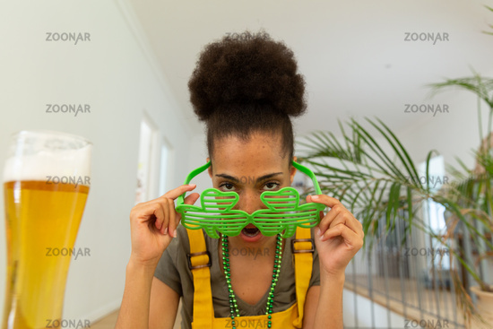 Mixed race woman celebrating st patrick's day making video call looking over shamrock glasses