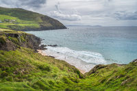 People swimming in turquoise coloured sea between cliffs in Dingle Peninsula