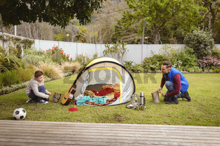 Caucasian father and son smiling while setting up a tent together in the garden