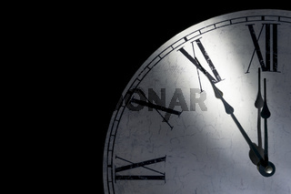 Detail of a vintage wall clock showing five minutes to midnight as a symbol for time running out