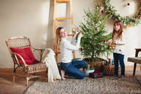 Joyful mother and lovely girl daughter in cozy knitted sweaters decorating Christmasmas fir tree with new year baubles and toys in living room