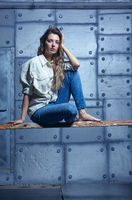 Portrait of young beautiful blonde woman is sitting on a board on metal wall background.
