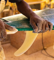 An African Craftsman surfboard Shaper working in a repair workshop