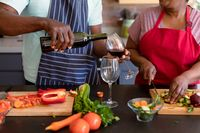 Midsection of african american senior couple cooking together in kitchen, drinking wine