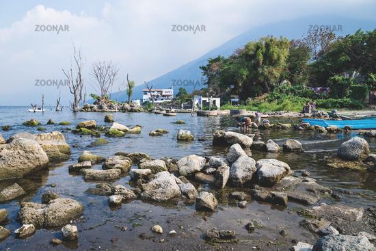Beach at lake atitlan with local people fishing and doing laundry, San Pedro La Laguna, Guatemala