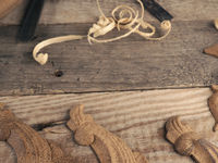 Carved oak decorative elements on a rustic workbench with chisels, wood working concept