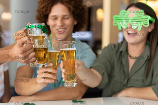 Diverse group of happy friends celebrating st patrick's day making toast with glasses of beer at bar
